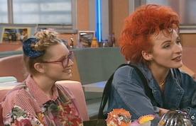 """Sophie Mounicot est """"la super copine de Maman"""", une sorte de vieille adulescente légèrement timbrée. Elle permet en tout cas à la bande d'aller voir Roch Voisine, et flirte un peu trop avec Jérôme. On connaîtra par la suite cette comédienne dans son excellent rôle dans la sitcom H. Si ce guest """"orangé"""" au sein de Premiers Baisers semble être une casserole pour la comédienne. On peut comprendre."""